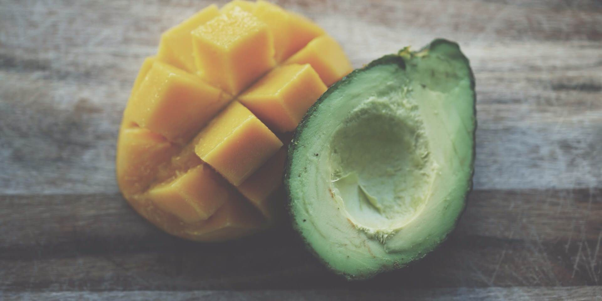 Mango and avocado on wooden table