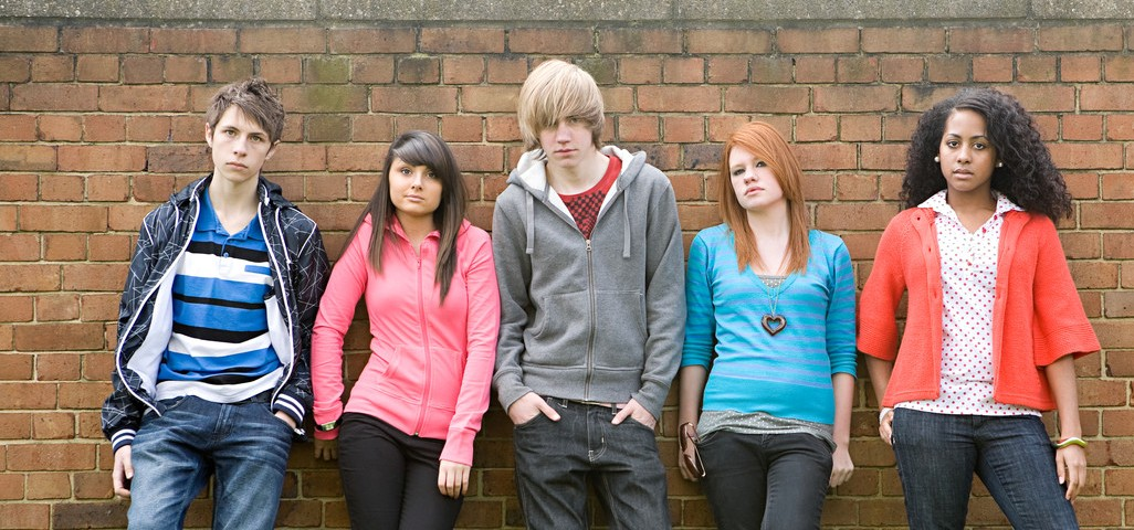 Teens standing by wall --- Image by © Image Source/Corbis
