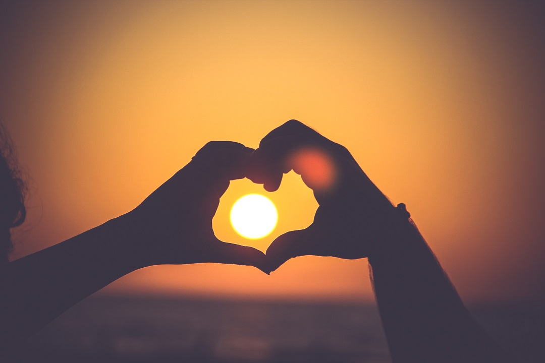 Hands in heart shape in front of sun