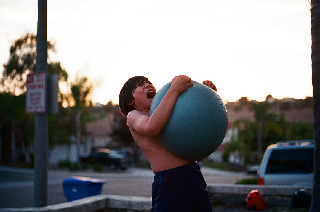 Young boy squeezing a large rubber ball