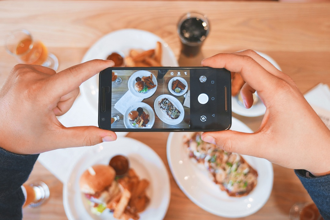 Person taking an artful picture of their lunch with an iPhone