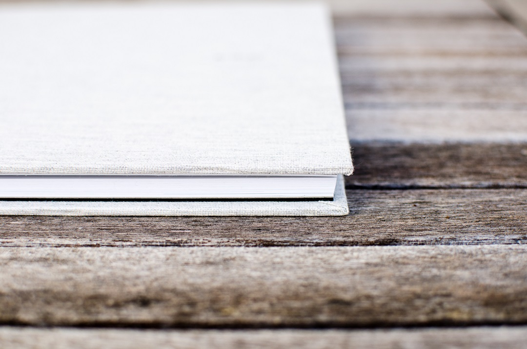 White cloth-covered book on a wooden table