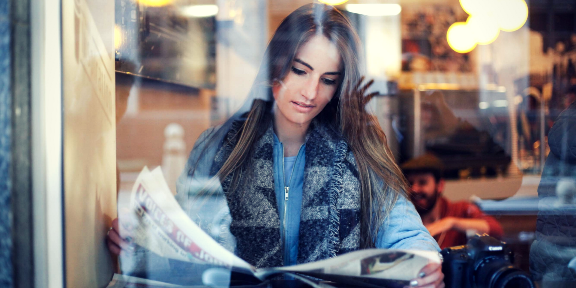 Woman in a coffee shop reading newspaper