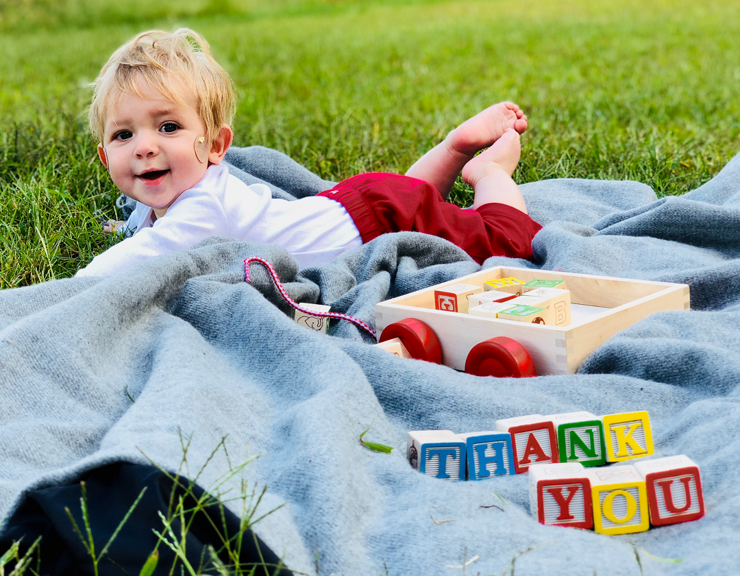 "Baby on blanket with blocks in the foreground spelling out ""thank you"""