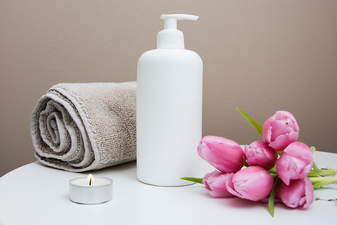 Towel, lotion, candle, and flowers on a table