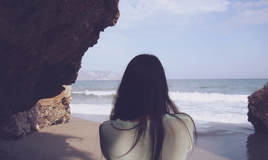 Woman standing under a cliff looking out at sea
