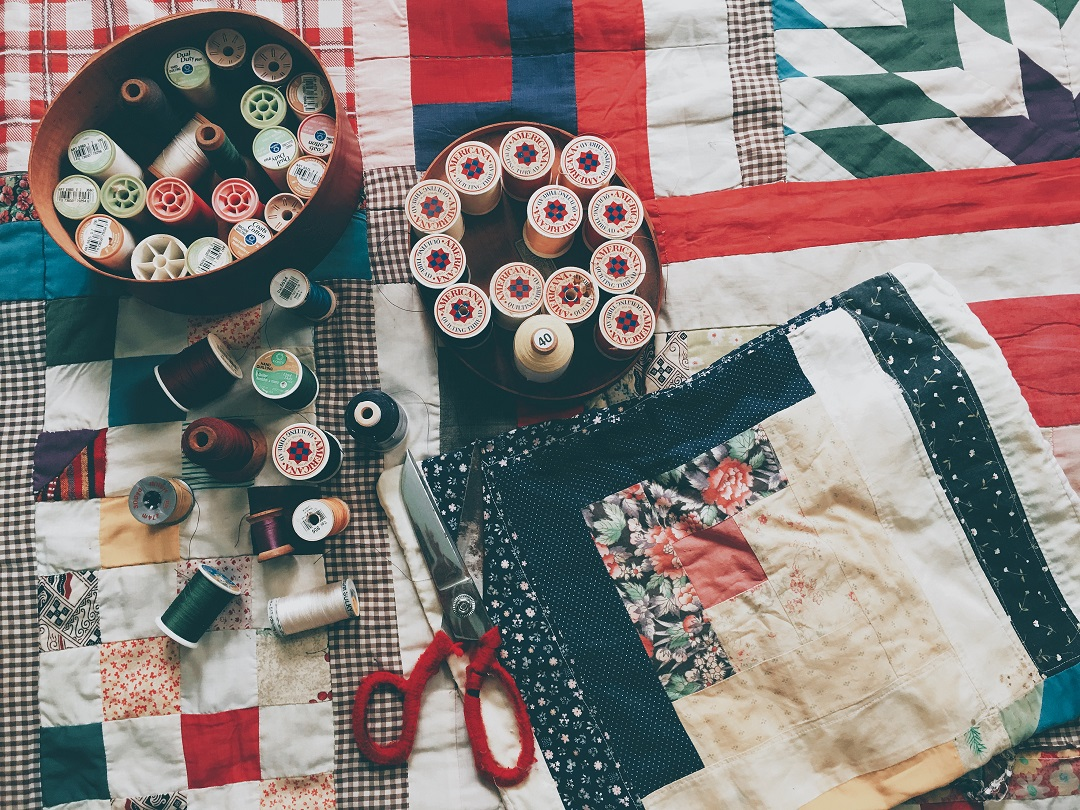 Spools of thread, scissors, and other quilting paraphernalia on a checked quilt.