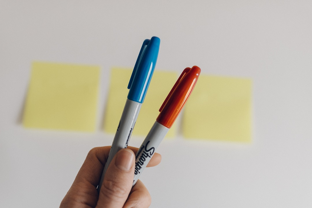 Hand holding two sharpies in front of wall of post it notes
