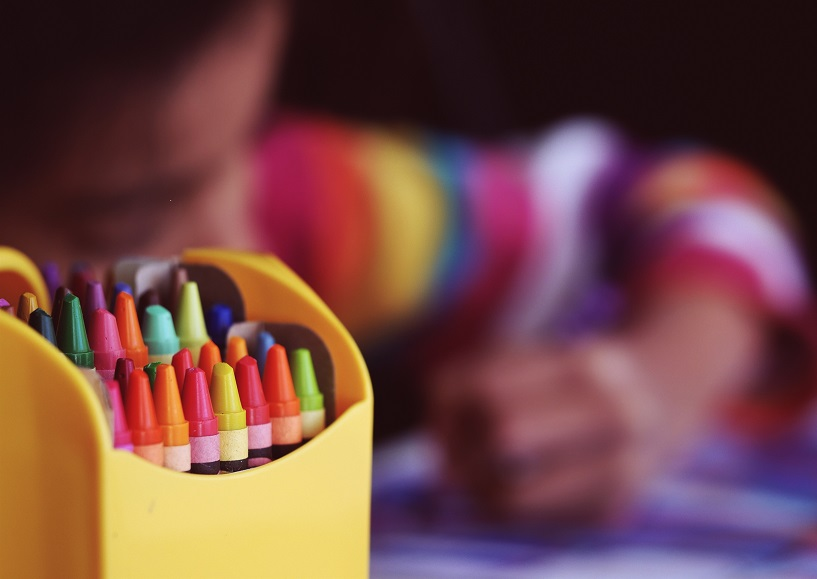 Macro shot of crayons, with blurred child in background coloring