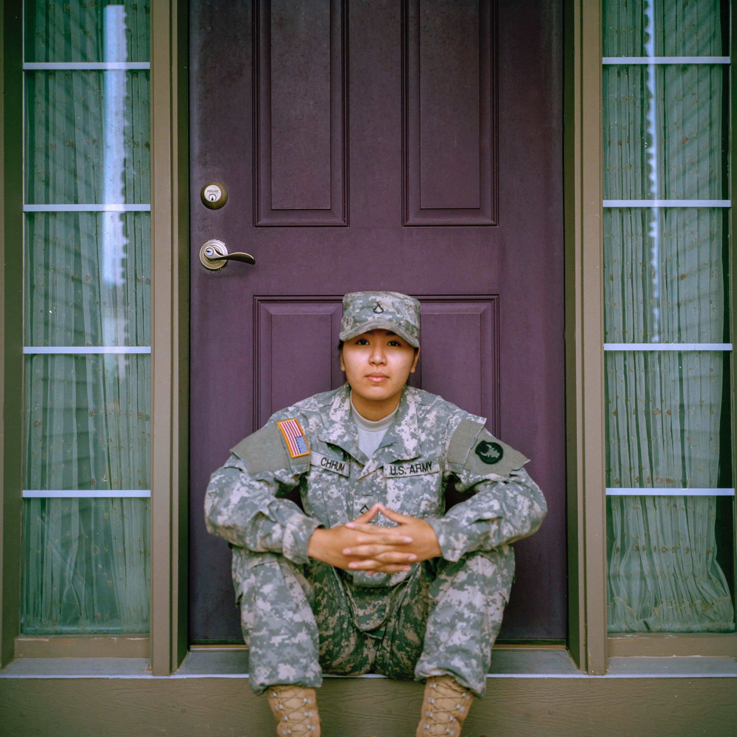 Female service member sitting in front of a doorway
