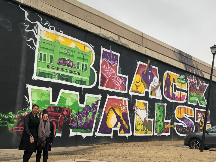 Qwynn, Co-Director of SMVF TA Center, and Jasmin, Consultant to the SMVF TA Center, in front of a Black Wall Street mural in Tulsa, Oklahoma, in 2019